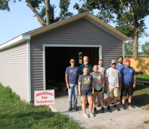 Carpentry students from LLCC-Taylorville pose with their instructor and representatives from Missions for Taylorville in front of the newly restored garage.
