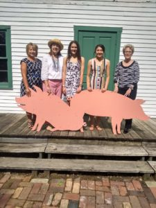 Standing on stage behind two wooden pigs are: l-r: Karen Sanders, vice-president of advancement and executive director, LLCC Foundation; Carol Alexander, author; Kennedie Cearlock and Deissy Booker, LLCC students and scholarship recipients; Dr. Charlotte Warren, LLCC president
