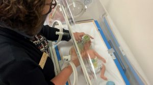 Jan Szoke, program director, demonstrates respiratory therapy on a premature  infant simulator.